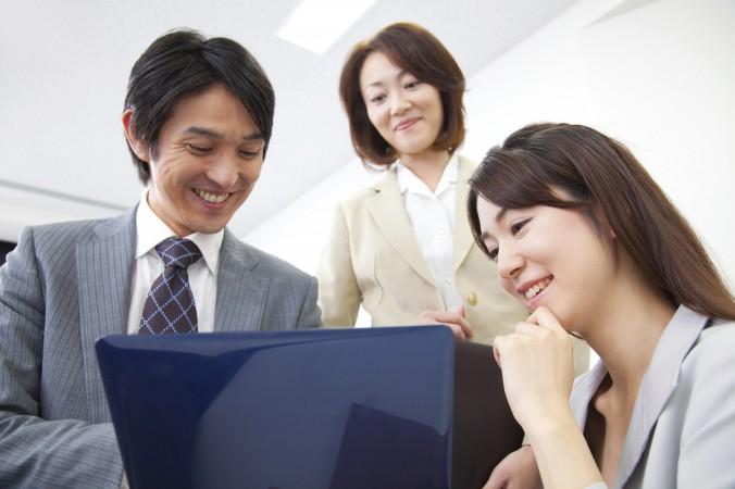 ノートパソコンを覗き込むビジネスマンとOL