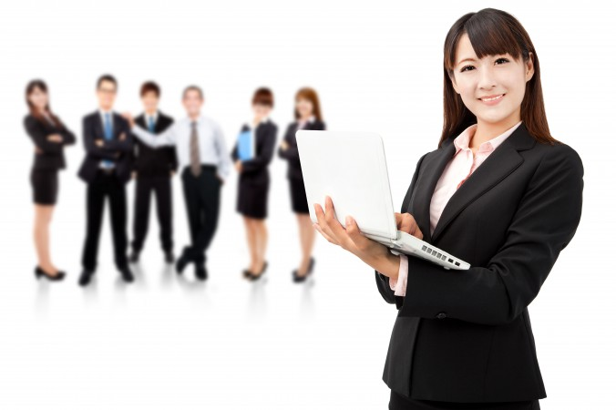 businesswoman holding laptop and business team
